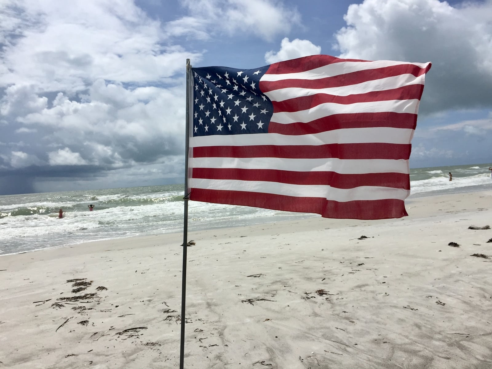 us a flag on beach during daytime
